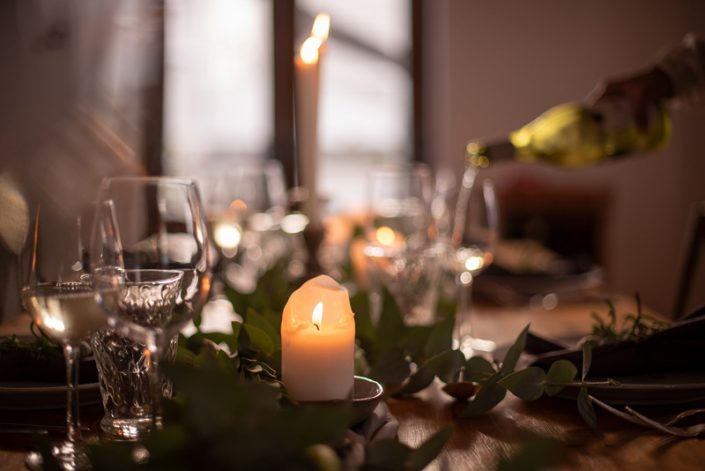 A candle on the table while a glass of wine is poured at The Homestead Venue